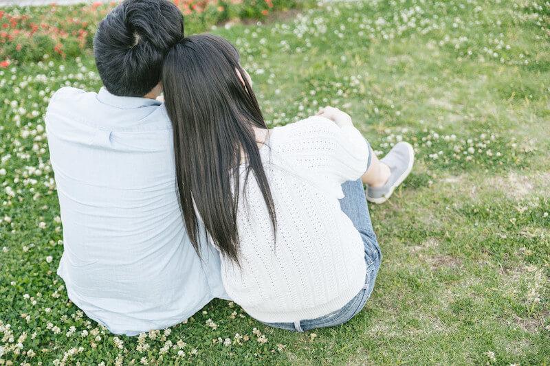 芝生でくつろぐ仲良しカップル